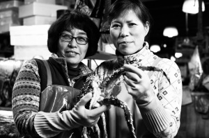 Sister and neighbouring store owners posing with a giant crab